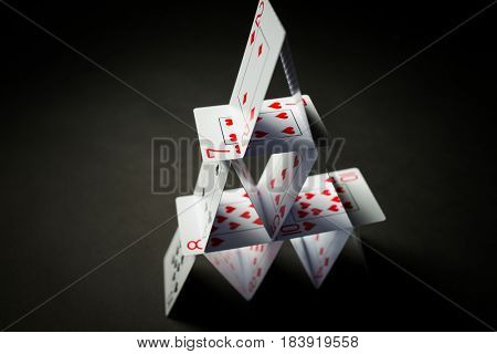 casino, gambling, games of chance, hazard and insecurity concept - house of playing cards over black background