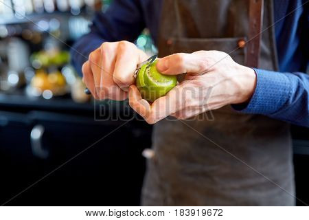 people and profession concept - bartender with peeler removing peel from lime at bar