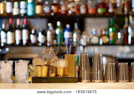 alcohol drinks, equipment and luxury concept - shakers, glasses with ice, stirrers and strainers on bar counter