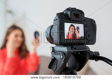 blogging, technology, videoblog and people concept - happy smiling woman or beauty blogger with eyebrow pencil, mirror and camera recording makeup  tutorial video at home