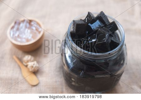 Grass jelly dessert in glass jar with ice (focus grass jelly)