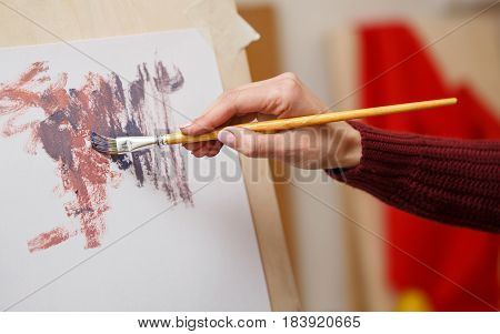 Girl draws an abstract painting in an art school. Hands close-up. Courses of drawing for adults.