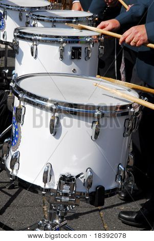 four white drums and drummers with moving drumsticks in action