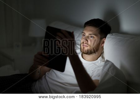 technology, internet, communication and people concept - young man with tablet pc computer in bed at home bedroom at night