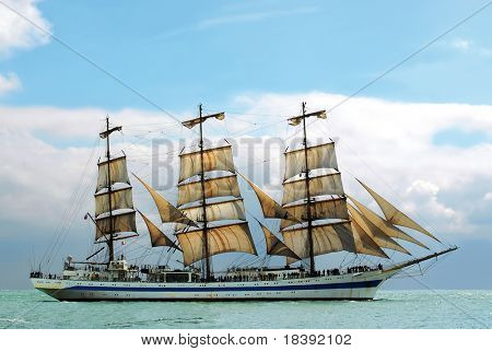 nostalgic sailboat sailing the ocean with cloudy and blue sky background