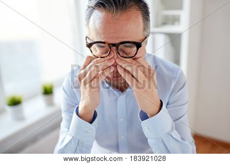 business, overwork, deadline and people concept - close up of tired businessman in eyeglasses rubbing eyes at office