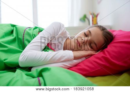 children, rest and people concept - girl sleeping in her bed at home