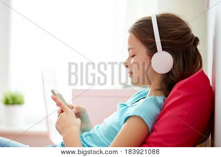 children, technology and people concept - happy girl with smartphone and headphones listening to music in bed at home