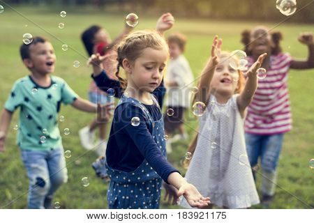 Group of kindergarten kids friends playing blowing bubbles fun