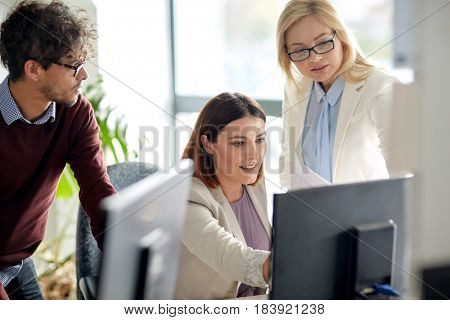 business, technology, teamwork and people concept - happy creative team with computer in office
