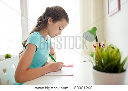 people, children, education and learning concept - girl writing to notebook at home