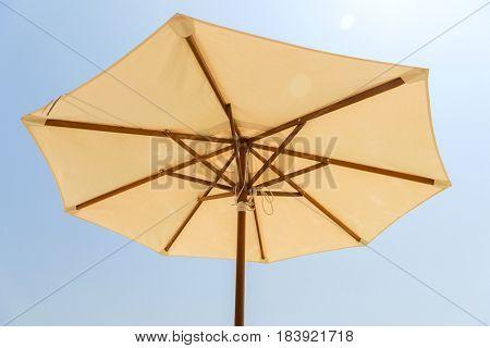 sunshade and beach equipment concept - parasol over blue sky