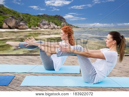 fitness, sport, yoga, people and healthy lifestyle concept - women making half-boat pose on mat outdoors over exotic tropical beach background