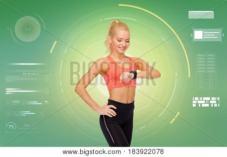 sport, fitness, technology, exercising and people concept - smiling woman looking at heart rate tracker or smartwatch on hand over green background