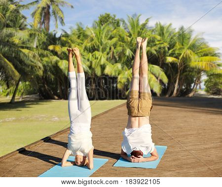 fitness, sport, yoga, people and healthy lifestyle concept - couple making headstand pose on mat over natural exotic background with palm trees