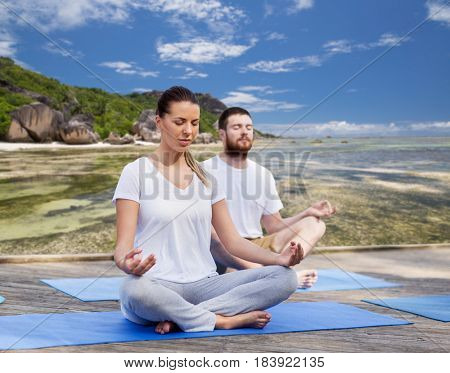 fitness, sport, yoga and healthy lifestyle concept - group of people meditating in lotus pose over exotic tropical beach background