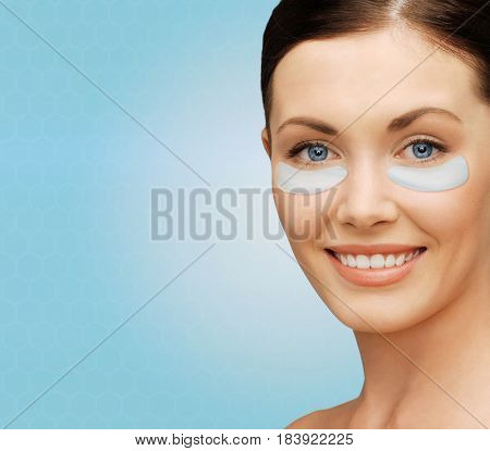 beauty, cosmetology, hydration, people and rejuvenation concept - close up of beautiful young woman face with hydrogel under-eye patches over blue background