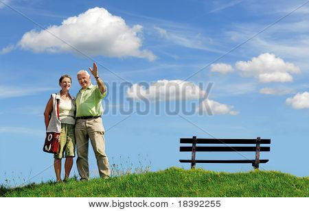 senior retired smiling couple, man greeting with his hand, walking outdoors on green grass hill with bench and white clouds on blue sky background