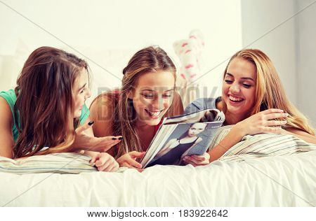 friendship, people and pajama party concept - happy friends or teenage girls reading magazine in bed at home