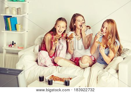friendship, people, pajama party, entertainment and junk food concept - happy friends or teenage girls eating pizza and watching movie or tv series at home
