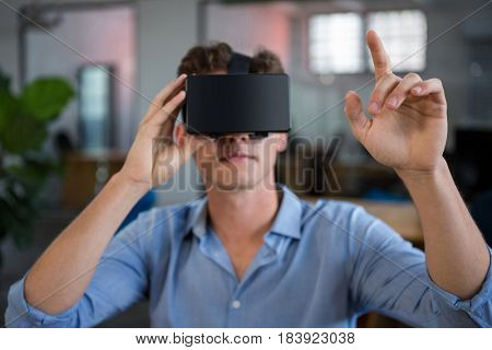Man using virtual reality headset in creative office