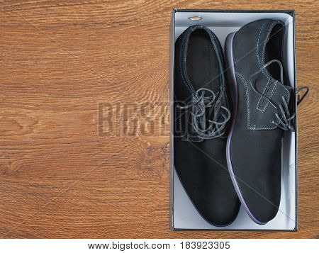 Black men's shoes in a colorful packaging on a wooden floor. The view from the top.