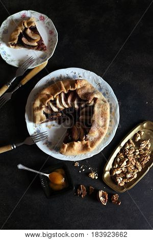 Still life with delicious apple pie, honey and walnuts on the dark background