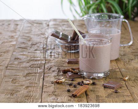Banana Smoothie With Cinnamon And Chocolate On Rustic Table.