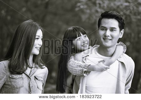 young asian family walking enjoying nature black and white.