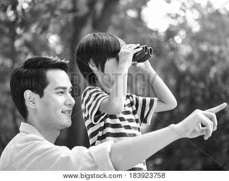 asian father and son using binoculars in park black and white.