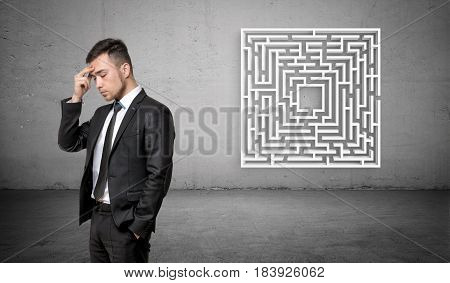 A businessman in deep thought with a white maze on concrete background behind him. Business planning. Problems and solutions. Unexpected difficulties.