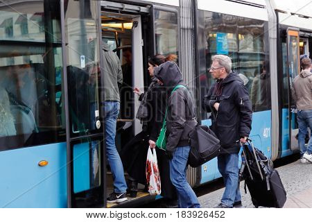 Gothenburg Sweden - April 16. 2017: Passengers enter a blue articulated tram ath the stop Drottningtorget.
