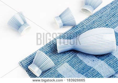 Sake bottle and cup on white background
