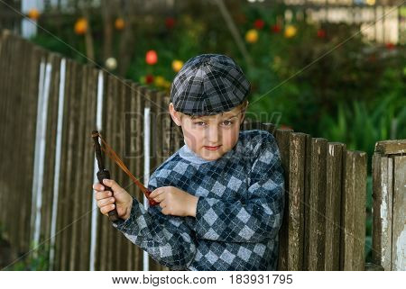 the little boy in the cap the bully with a slingshot in the hands