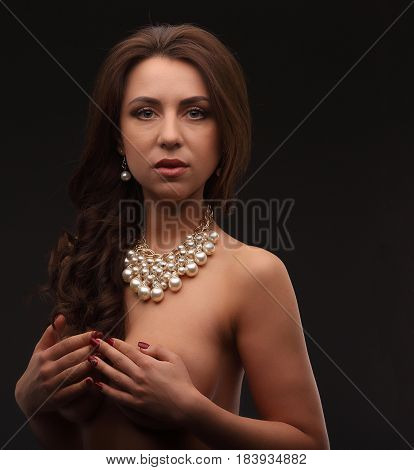 Young Brunette Model Over Dark Background Naked With Necklace Hiding Her Chest And Looking To Camera