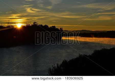 Beautiful sunrise and its rays at the river. Sunshine beams in misty foggy river at early morning.