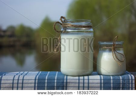 wo jars of fermented milk product against the background of the river