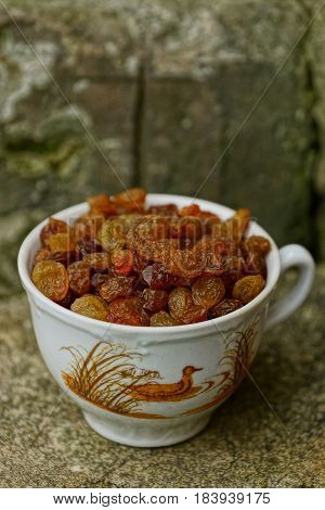A cup of raisins standing on a stone
