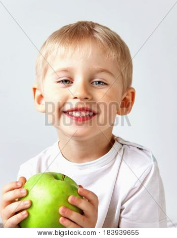 Small Boy Holds A Big Green Apple, Healthy Food And Vitamins, Smiling,