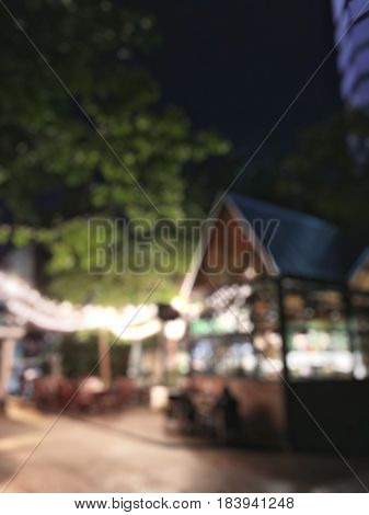 Blur Bokeh Light Of Retro Restaurant With Green Environment In The Night Time.