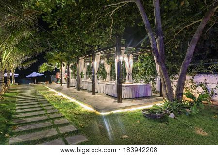 MUINE VIETNAM - MARCH 25 2017. Romantic garden chairs with candles. Relax on the garden. Garden with deck chairs for relaxing and a smoking pipe. c