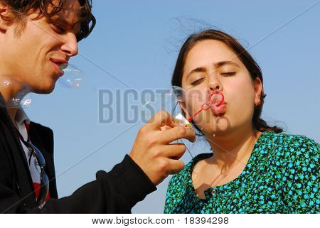 Concept: stay young. Man in his twenties lets his girlfriend blow soap bubbles on blue sky background