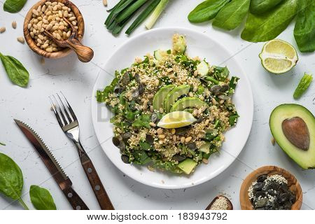Fresh quinoa salad with spinach avocado seeds and Pine nuts. Clean eating detox and vegetarian food. Top view on white.