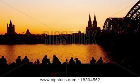 Silhouettes of people watching sunset in Cologne with view on the 'dom' cathedral and the 'hohenzollern' railway bridge over river rhine