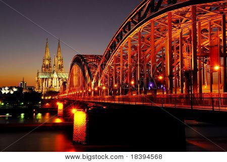 View on the 'dom' cathedral and the floodlighted 'hohenzollern' railway bridge over river rhine in Cologne at night