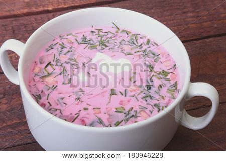 Popular spring cold soup okroshka with yoghurt. Okroshka in a bowl on wooden table. Selective focus.