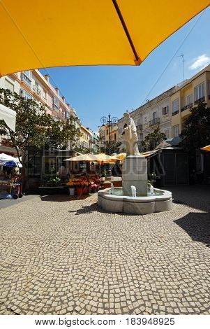 CADIZ, SPAIN - SPETMEBER 8, 2008 - Marble fountain in the Plaza de las Flores with flower stalls to the rear Cadiz Cadiz Province Andalusia Spain Western Europe, September 8, 2008.