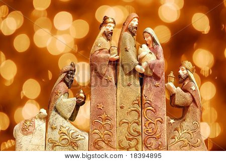 Religious christmas group with 3 kings, joseph, mary, baby jesus and a sheep on bokeh light background