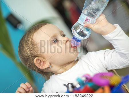 Adorable kid girl drinking water from bottle. Adheres to the drinking regime