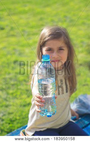 Pretty little girl holds bottle of water